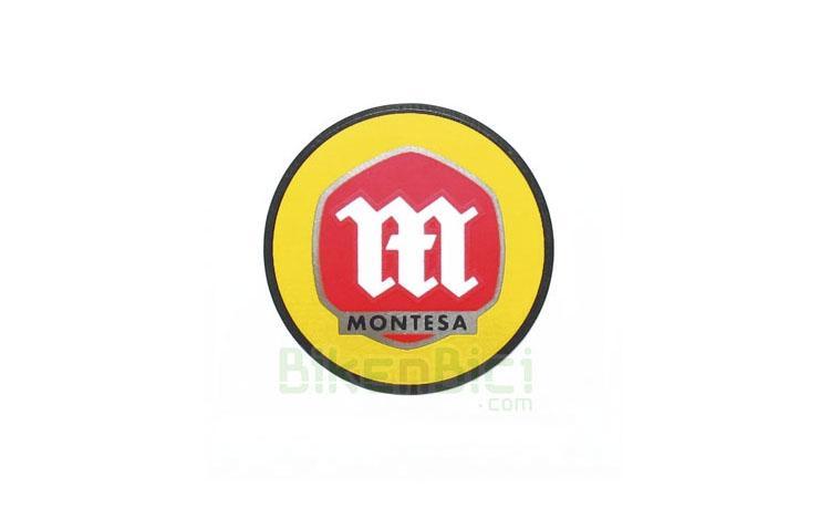 Calcas Trialsin MONTESA PLACA PORTANÚMEROS 27mm - Calca Montesa utilizada en la placa portanúmeros de los modelos de Montesa que usan dicha placa. Adhesiva. 27mm de diámetro.